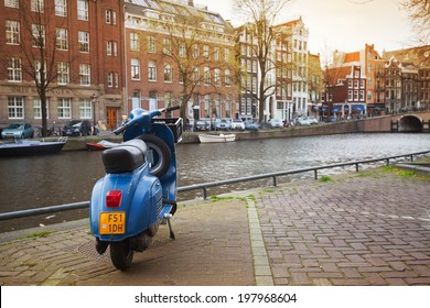 AMSTERDAM, NETHERLANDS - MARCH 19, 2014: blue Vespa scooter stands parked on the canal coast embankment