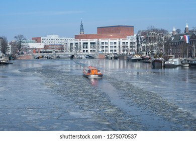 Amsterdam, The Netherlands - March 2, 2018: canal cruise on frozen river Amstel on a very cold winter day.
