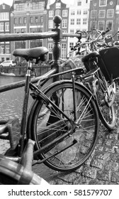 AMSTERDAM, NETHERLANDS - MARCH 2016: Bicycle leaning on railings next to canal
