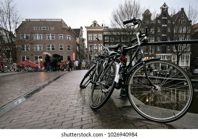 Amsterdam, Netherlands - March 23, 2008: black bicycles wet from rain parked on bridge over one of many canals with houses in the back.