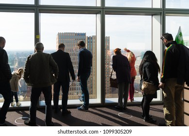 AMSTERDAM, NETHERLANDS - MARCH 25, 2017: Unknown people looking through the glass of a skyscraper during the open tower day, a yearly event when prominent towers open their doors