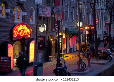 AMSTERDAM, NETHERLANDS - MARCH 26: Red light district at night on March 26, 2013 in Amsterdam. Red light district is a part of city Amsterdam where is a lot of prostitution and sexoriented businesses.