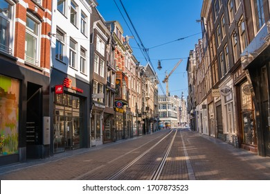 Amsterdam / The Netherlands - March 28, 2020: Empty Leidsestraat in Amsterdam center during corona crisis. The Leidsestraat is normally one of the busiest shopping streets for tourists in Amsterdam.