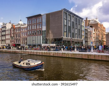 Amsterdam, Netherlands, March 30, 2013: Anne Frank House museum with queue of visitors and a boat sailing by in the canal
