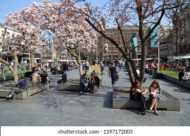 Amsterdam, The Netherlands - March 31, 2017: Tourists sit on the Rembrandtplein square in Amsterdam, The Netherlands on March 31, 2017