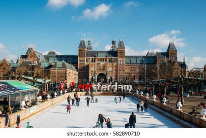 AMSTERDAM, THE NETHERLANDS - March 7, 2015: Many people skate on winter ice skating rink in front of the Rijksmuseum, with a old film camera color style with grain