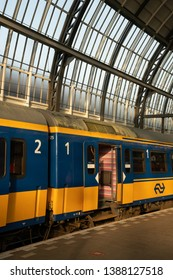 Amsterdam / The Netherlands - May 1, 2019: Typical Dutch NS Intercity train in yellow and blue color at Amsterdam Central Station, The Netherlands
