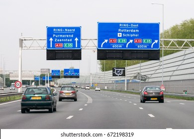 AMSTERDAM, NETHERLANDS - MAY 10, 2016: Traffic on motorway interchange A1-A10 and overhead route information signs, Amsterdam, North Holland