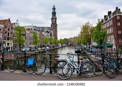 Amsterdam / Netherlands — May 10, 2017: view of the Prinsengracht canal in Amsterdam with the Dutch Protestant Westerkerk church and bikes in the foreground