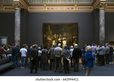 AMSTERDAM, NETHERLANDS - MAY 10, 2017: People watching the picture The Night Watch or The Militia Company of Captain Frans Banning Cocq of Rembrandt, in the Rijksmuseum