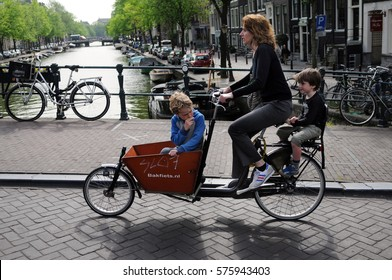 AMSTERDAM, NETHERLANDS - MAY 12, 2011: Mother with two children riding bicycles in historical part in Amsterdam.