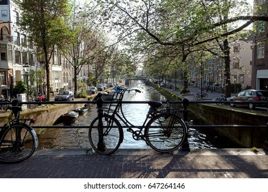 AMSTERDAM, NETHERLANDS - MAY 13, 2017: View from the bridge to the canal and the next bridge