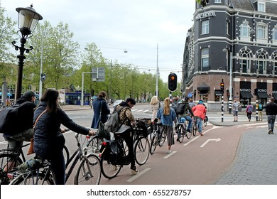 AMSTERDAM, NETHERLANDS - MAY 15, 2017: Queue of cyclists in front of a special traffic light on the bike path