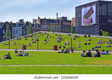 Amsterdam, The Netherlands - May 20, 2018: Amsterdam Stedelijk Museum for modern, contemporary art and design, new wing of the museum and people resting on the lawn of Museumplein