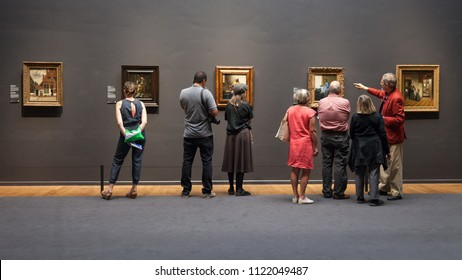 Amsterdam, Netherlands - May 2018: A museum guide and tourists look at the artwork of Johannes Vermeer, inside the Rijksmuseum