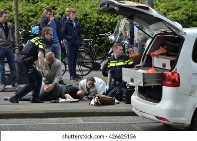 Amsterdam, Netherlands - May 21, 2016: An injured cyclist lying on the ground after being hit by a car, surrounded by two police officers and other pass byers, next to an open police vehicle.