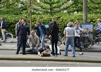 Amsterdam, Netherlands - May 21, 2016: View of a crowd surrounding an injured cyclist lying on the ground after being hit by a car, in a busy suburban street.