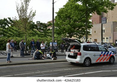 Amsterdam, Netherlands - May 21, 2016: Distant view of an injured cyclist lying on the ground after being hit by a car, surrounded by pass byers, two police officers and a police car.