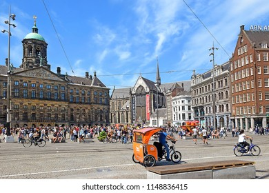 Amsterdam, The Netherlands - May 21, 2018: tourist and locals visiting the Dam square with in the background the old City Hall and now the Royal Palace. this is one of the most popular meeting points