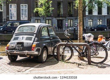 Amsterdam, Netherlands - May 21, 2018: Back of the black old rusty Italian small car Fiat 500L or Lusso parked at one of the Amsterdam canals near bicycle.