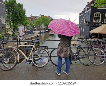 AMSTERDAM, NETHERLANDS - MAY 22, 2018: Tourist sightseeing in rainy Amsterdam in the Netherlands
