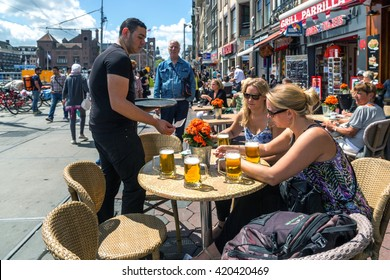 Amsterdam, Netherlands - May 22nd 2014 - Tourists enjoy a drink in downtown Amsterdam in a blue sky day. Netherlands