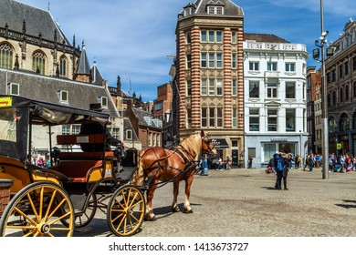 Amsterdam, The Netherlands - May 23, 2019: The horse carriage with the coachman waiting for tourists on the Dam Square, the main square of the city.