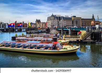 Amsterdam, Netherlands - May 23, 2019: View of Canal Boat City Hopper near the Central Station of Amsterdam, center district of city.