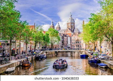 Amsterdam / Netherlands - May 24, 2017: Tour boat at famous dutch canal on a sunny day, surrounded by traditional old buildings, in Red Light District.
