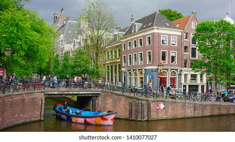 Amsterdam, Netherlands - May 24 2019: A colorful boat passing through the canal with people engaging daily activities.