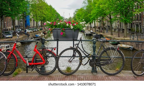 Amsterdam, Netherlands - May 24 2019: Full bloom flowers in a pot on a canal bridge between two parked bicycles.