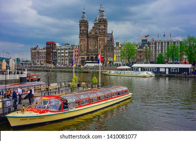 Amsterdam, Netherlands - May 24 2019: A passenger tour boat parked by the canal overlooking the Church of Saint Nicholas.