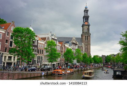 Amsterdam, Netherlands - May 24 2019:   The famous Westerkerk or as known as Westertorn tower overlooking the canal in Amsterdam.