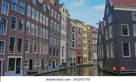 Amsterdam, Netherlands - May 24 2019: A row of Amsterdam most iconic houses by the canal.