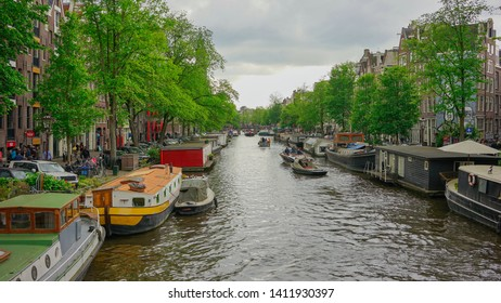 Amsterdam, Netherlands - May 24 2019:   Iconic Amsterdam house boats docked along the canal.