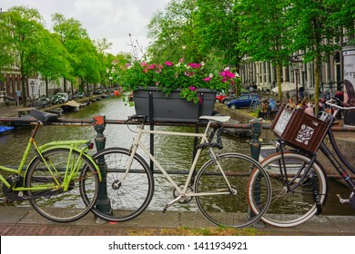Amsterdam, Netherlands - May 24 2019: Full bloom flowers in a pot on a canal bridge between parked bicycles.