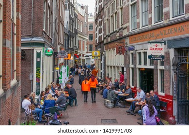 Amsterdam, Netherlands - May 24 2019:  Streets of Amsterdam by the canal with people engaging in daily activity.