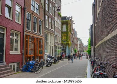 Amsterdam, Netherlands - May 24 2019:  Streets of Amsterdam with people engaging in daily activity.