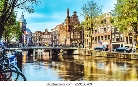 AMSTERDAM, NETHERLANDS - MAY 25, 2017:The most famous canals and embankments of Amsterdam city during sunset. General view of the cityscape and traditional Netherlands architecture on May 25, 2017