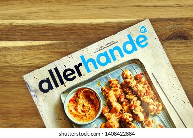 Amsterdam, the Netherlands - May 26, 2019: In-house magazine Allerhande of Dutch grocery chain Albert Hijen, against a wooden background.