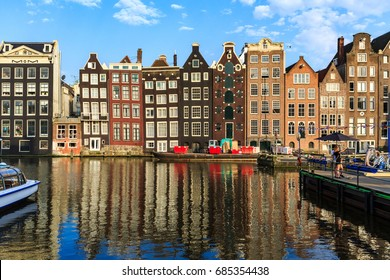 AMSTERDAM, NETHERLANDS - MAY 27, 2017: Exterior view of buildings at Damrak street in the old town part of Amsterdam on May 27, 2017. Amsterdam is popular by tourist for historical houses and canals.