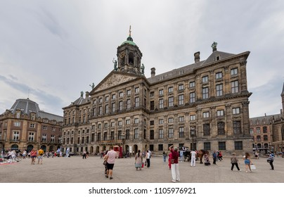AMSTERDAM, NETHERLANDS - MAY 27, 2018: Tourists walk in front of the Royal Palace (in Dutch: Koninklijk Paleis) at the Dam Square.