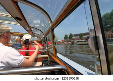 Amsterdam, the Netherlands - May 29, 2018: Amsterdam canal boat cruise is popular among tourists to explore the city in a deeper perspective of its history with audio tour explanation.