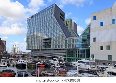 AMSTERDAM, NETHERLANDS - MAY 3, 2016: Modern hotel Room Mate Aitana and yachts on IJdock peninsula in Amsterdam, Netherlands