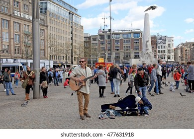 AMSTERDAM, NETHERLANDS - MAY 3, 2016: Street musician and tourists on Dam square, historical center of the city in Amsterdam, Netherlands. The place is historical center of the city with Royal Palace.