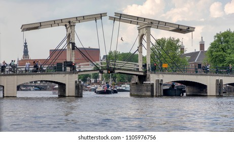 AMSTERDAM, NETHERLANDS - MAY 30, 2018: Sightseeing boats pass under the Magere Brug Bridge.