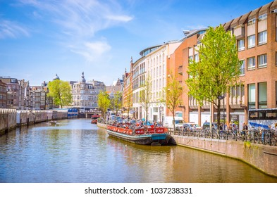AMSTERDAM, NETHERLANDS - MAY 5, 2016: Traditional old buildings and boats in Amsterdam, Netherlands