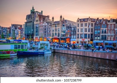 AMSTERDAM, NETHERLANDS - MAY 5, 2016: Traditional old buildings and boats at sunset in Amsterdam