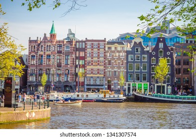 AMSTERDAM, NETHERLANDS - MAY 5, 2016: Traditional old buildings and and boats in Amsterdam, Netherlands