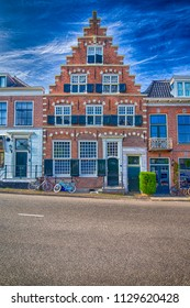 Amsterdam, Netherlands – May 6, 2017: Traditional Red Brick Dutch House with Classic Ledged Gable in the Forefront. Line of Bicycles at Doors in Amsterdam, The Netherlands